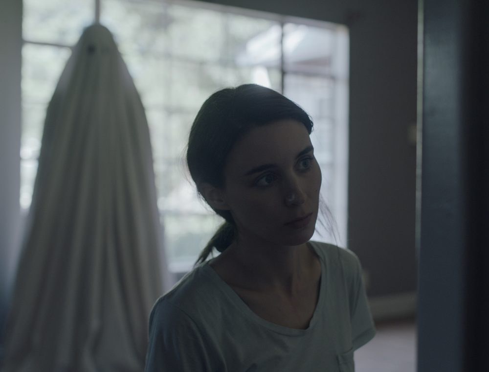 Rooney Mara with the ghost of Casey Affleck's character in the background. (Courtesy Bret Curry/A24)