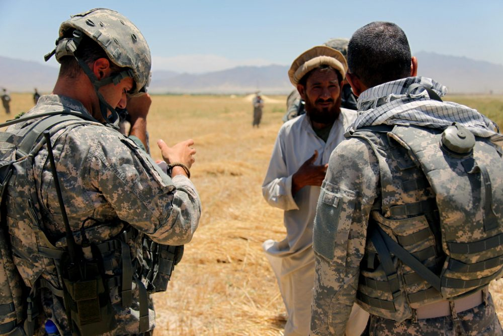 An Afghan interpreter (right) helps a U.S. soldier gather information from a local resident in this 2010 photo. (Corey Idleburg/U.S. Army)