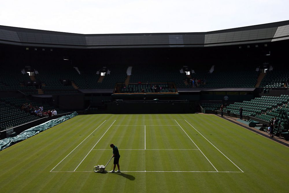 A groundsman paints a line on Centre Court on on Day 1 of Wimbledon tennis tournament on June 29, 2015 in London, England. (Carl Court/Getty Images)