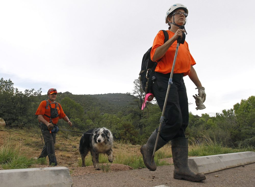 Members of the Tonto Rim Search and Rescue team exit a section of forest after searching along the banks of the East Verde River for victims of a flash flood, Sunday, July 16, 2017, in Payson, Ariz. Search and rescue crews, including 40 people on foot and others in a helicopter, have recovered bodies of children and adults, some as far as two miles down the river after Saturday's flash flooding poured over a popular swimming area inside the Tonto National Forest in central Arizona. (Ralph Freso/AP)