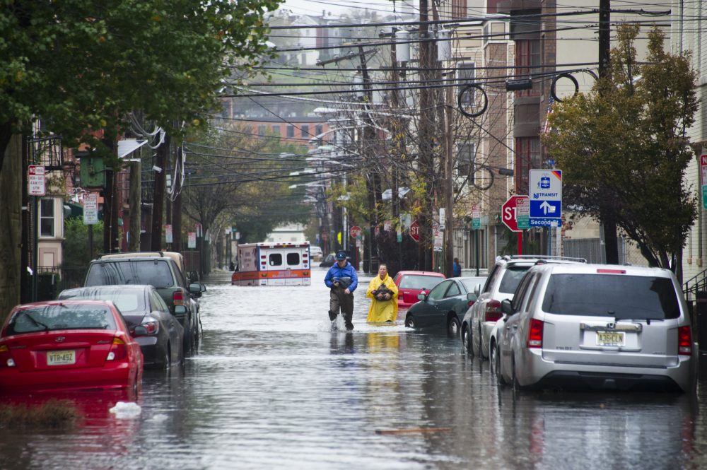 Residents walk through flood water and past a stalled ambulance in the  aftermath of Superstorm Sandy on Tuesday, Oct. 30, 2012 in Hoboken, NJ. (Charles Sykes/AP)