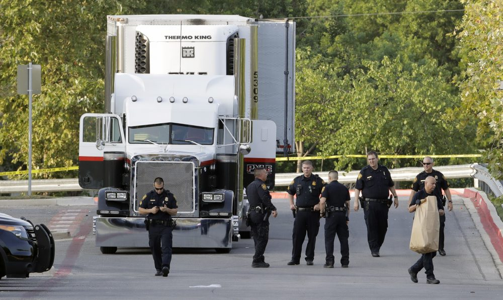 San Antonio police officers investigate the scene where nine people were found dead in a tractor-trailer loaded with at least 30 others outside a Wal-Mart store in stifling summer heat in what police are calling a horrific human trafficking case, Sunday, July 23, 2017, in San Antonio. (Eric Gay/AP)