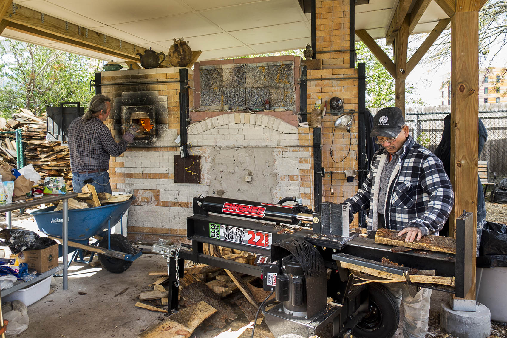 Yary Livan works at his kiln. His student John Kondra loads wood into the stone fireplace. (Andrea Shea/WBUR)