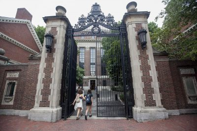 Students enter a side gate at Harvard University (Joe Difazio/WBUR)