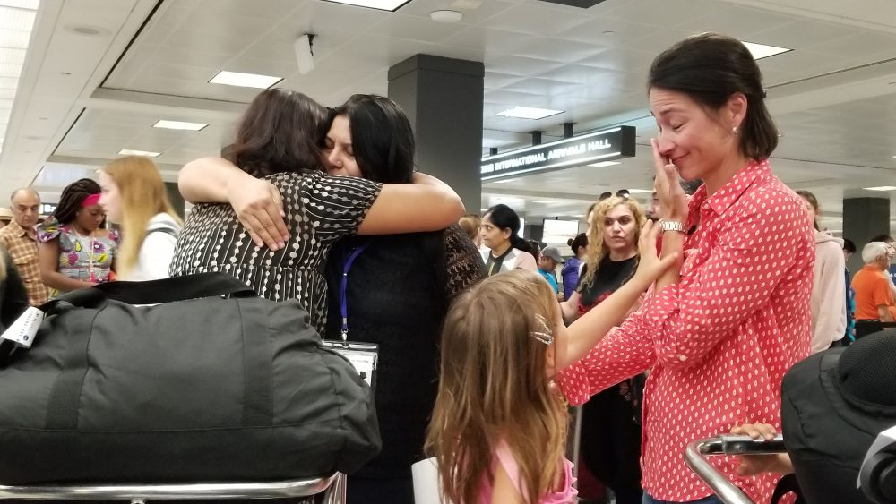 Sisters Rahila, left, and Shaista Sadiq, right, embrace at Dulles Airport as family friend Kristin Kim Bart looks on. The sisters went through a two year vetting process before being admitted as refugees to the U.S. Now, they're among the last refugees to be resettled in the before new refugee admissions guidelines go into effect next week. (Carmel Delshad/WAMU)