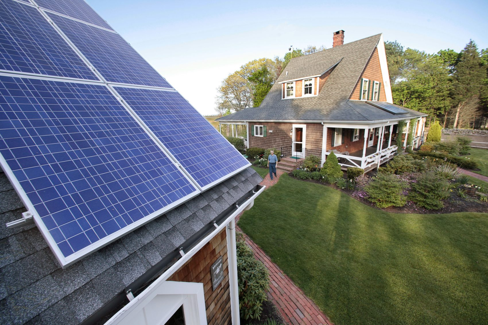 In this May 8, 2009 photo, Len Bicknell walks from his house to his garage where his solar energy panels are mounted on the roof in Marshfield, Mass. Bicknell's home is fitted with both thermal panels for hot water production and electric solar panels for energy production. (Stephan Savoia/AP)