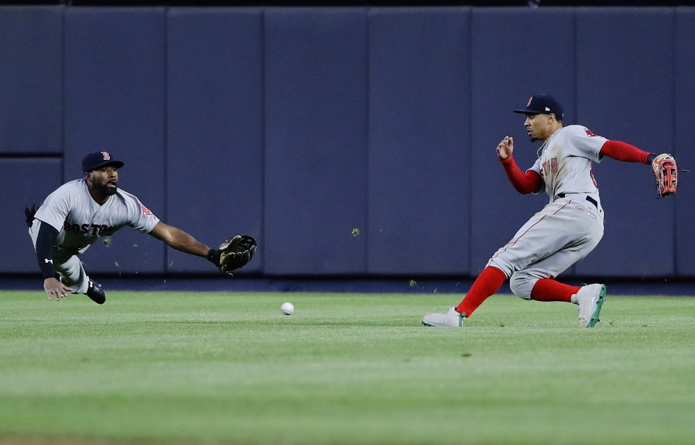 Boston Red Sox center fielder Jackie Bradley Jr., left, dives to catch a ball hit by New York Yankees' Didi Gregorius for a single as right fielder Mookie Betts, right, watches during the second inning of a baseball game Thursday, June 8, 2017, in New York. (AP Photo/Frank Franklin II)
