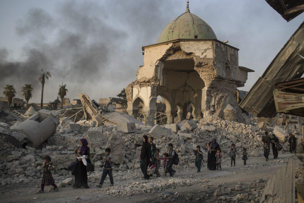Fleeing Iraqi civilians walk past the heavily damaged al-Nuri mosque in the Old City of Mosul, Iraq, Tuesday, July 4, 2017. (Felipe Dana/ AP)