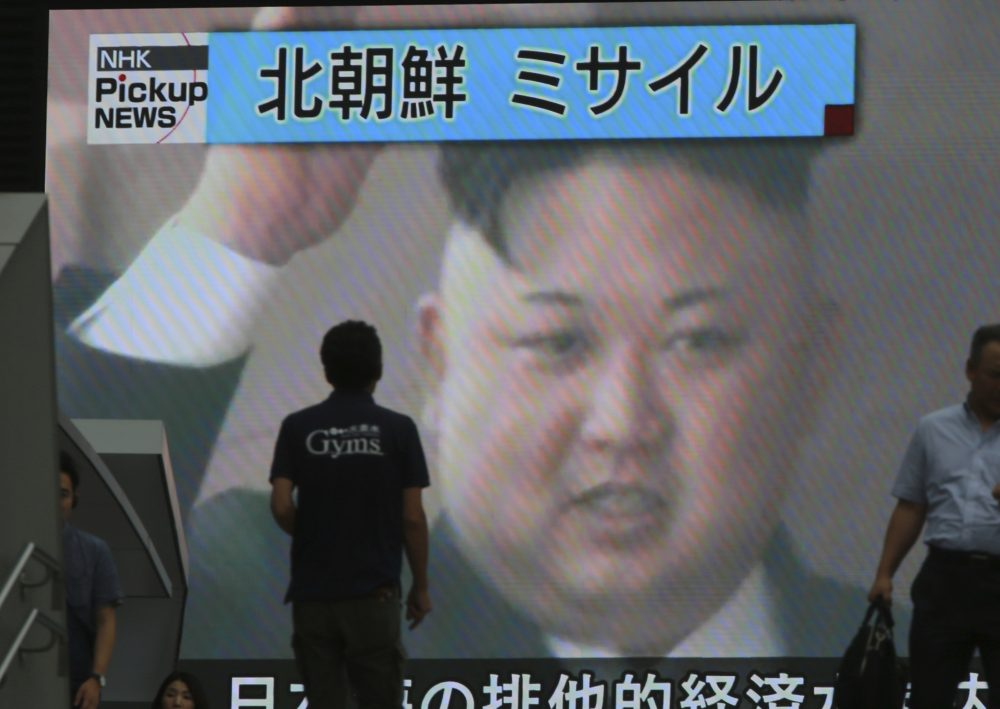 """In this Tuesday, July 4, 2017 photo, people walk in front of an image of North Korean leader Kim Jong Un shown on a large screen as a TV news reports the North Korea's missile test which landed in the waters of Japan's economic zone, in Tokyo. Despite U.S. President Donald Trump's hopes for China's help in dealing with North Korea and his recent tough talk on the matter, the two sides seem to be growing further apart as their approaches and concerns diverge. China shows no sign of caving in to U.S. pressure to tighten the screws on North Korea, while the North's recent missile tests have done little to rattle Beijing. China's bottom line continues to hold: no to any measures that might topple Kim Jong Un's hard-line communist regime. The top banner reads: """"North Korea Missile."""" (Eugene Hoshiko/AP)"""