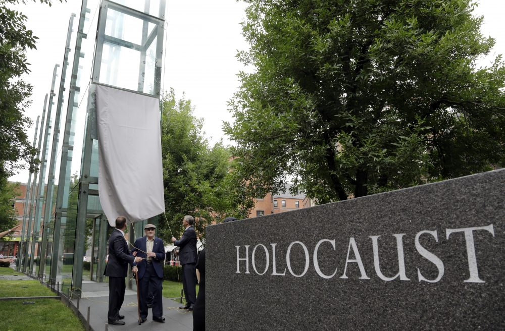 Holocaust survivor Steve Ross, center, founder of the New England Holocaust Memorial, is flanked by Boston Mayor Marty Walsh, left, and Massachusetts Gov. Charlie Baker Tuesday during a a rededication ceremony for the repaired New England Holocaust Memorial in Boston. One of the glass panes in the memorial was damaged by a vandal last month. (Elise Amendola/AP)