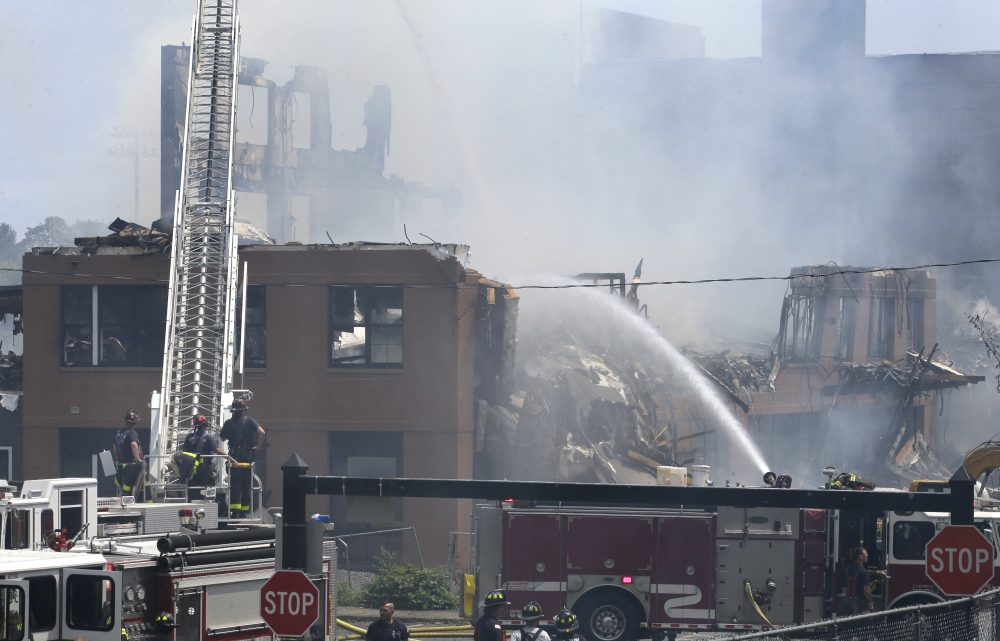 Firefighters pour water on the destroyed remains of an under-construction apartment complex Sunday in Waltham. (Steven Senne/AP)