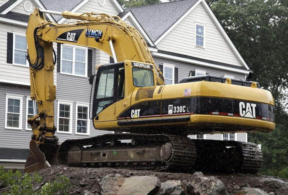 In this July 24, 2017, photo, a Caterpillar excavator rests at a housing construction site in North Andover, Mass. (AP Photo/Elise Amendola)