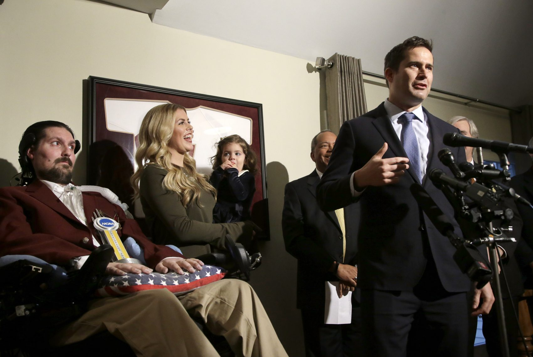 U.S. Rep. Seth Moulton, D-Mass., right, faces reporters as former Boston College baseball captain Pete Frates, left, and his wife Julie, center, and daughter Lucy, look on during ceremonies held to honor Frates with the 2017 NCAA Inspiration Award, Tuesday, Dec. 13, 2016, at their home in Beverly, Mass. (Steven Senne/AP)