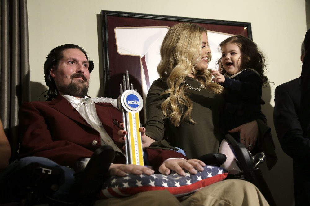 Pete Frates appears with his wife Julie and their 2-year-old daughter Lucy moments after he was presented with the 2017 NCAA Inspiration Award, on Dec. 13, 2016, at their home in Beverly. (Steven Senne/AP)