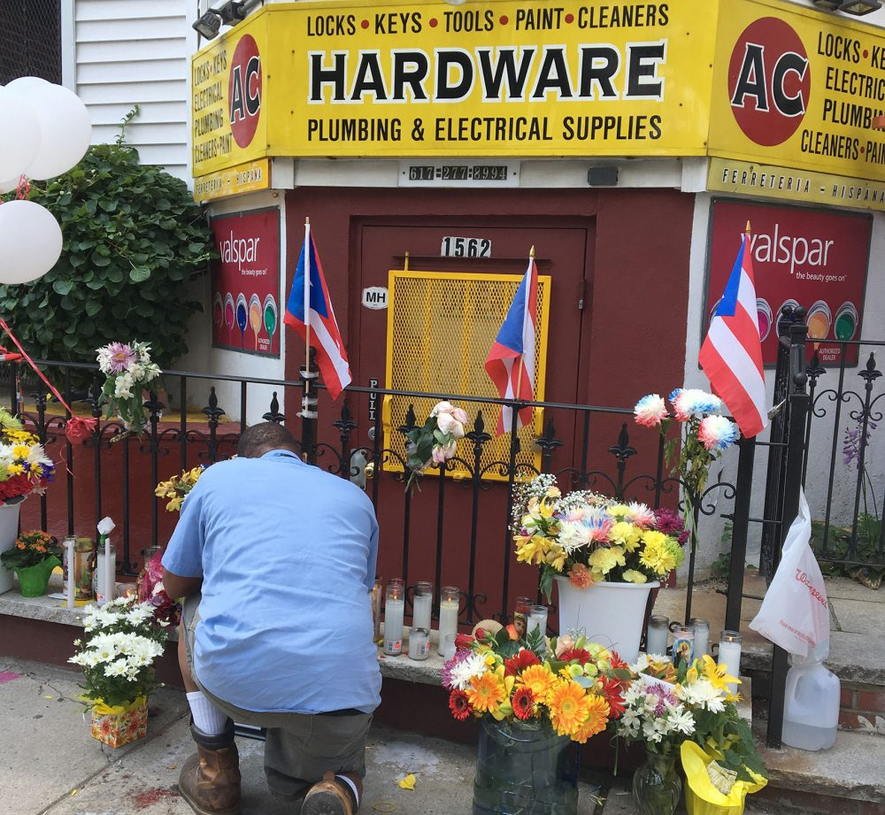 A man tends to a growing memorial Wednesday for Andres Cruz, who was fatally shot during an apparent robbery of his AC Hardware store in Boston's Mission Hill. (Anthony Brooks/WBUR)
