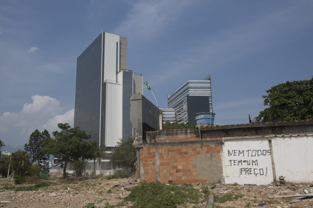 "A demolished house with a sign that translates to, ""Not everybody has a price"" stands in front of the Olympic Media Center building. (Silvia Izquierdo/AP)"