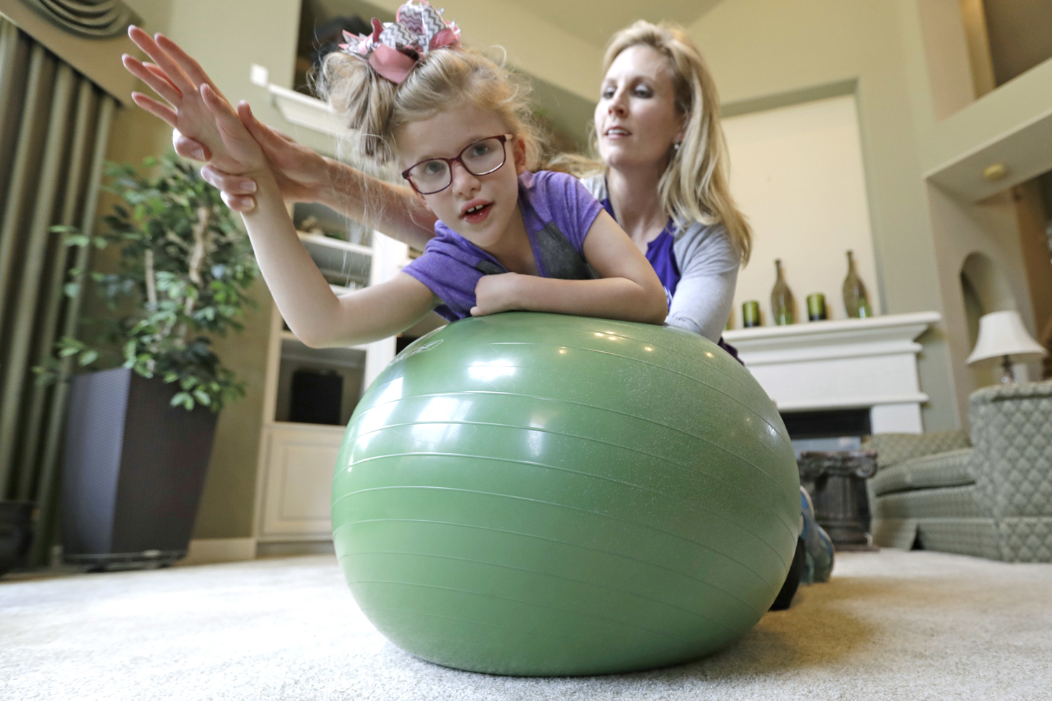 Stacey English, right, works on balance and core strength with her 7-year-old daughter, Addison, in Houston on Friday, June 23, 2017. Texas children with special needs like Addison have lost critical services since the state implemented $350 million in Medicaid cuts to speech, occupational, and physical therapy in December. (David J. Phillip/AP)