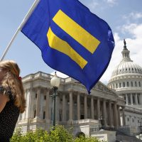 """A supporter of LGBT rights holds up an """"equality flag"""" on Capitol Hill on Wednesday. (Jacquelyn Martin/AP)"""