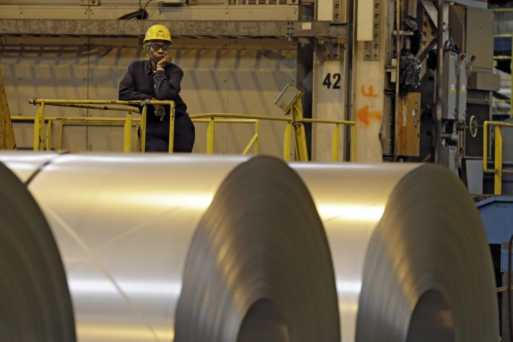 An employee looks on from behind coils of steel at the ArcelorMittal Steel's hot dip galvanizing line in Cuyahoga Heights, Ohio Friday, Feb. 15, 2013. (Mark Duncan/AP)
