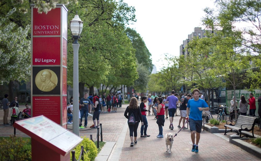 Students walk by a Boston University sign on Commonwealth Ave. (Robin Lubbock/WBUR)