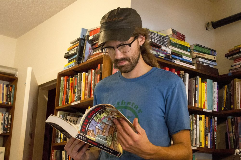 Anders Aughey browses for books at the Lucy Parsons Center bookstore in Jamaica Plain. (Kathleen Dubos for WBUR)