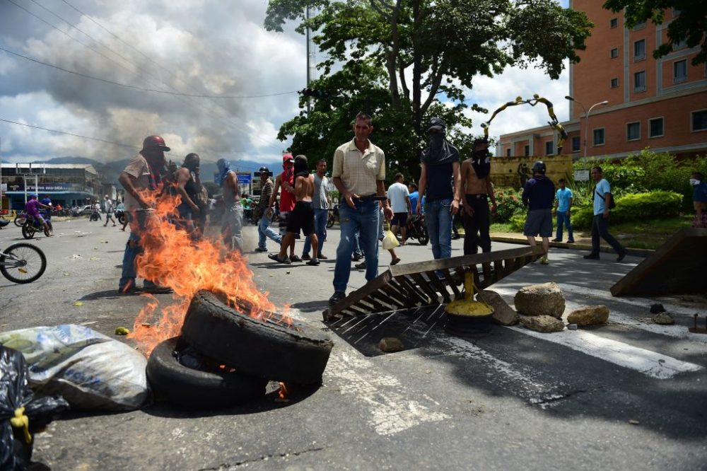 """Anti-government activists set up a barricade in the streets of Venezuela's third city, Valencia, on Aug. 6, 2017, a day after a new assembly with supreme powers and loyal to President Nicolas Maduro started functioning in the country. In a video posted online earlier, allegedly at an army base used by the National Bolivarian Armed Forces in Valencia, a man presenting himself as an army captain declared a """"legitimate rebellion ... to reject the murderous tyranny of Nicolas Maduro"""" and demanded a transitional government and """"free elections."""" After the video surfaced, military chiefs said troops had put down the """"terrorist"""" attack. (Ronaldo Schemidt/AFP/Getty Images)"""