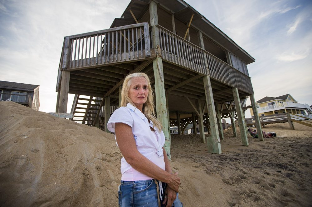 Freve Pace stands in front of the house she once owned but sold because the ocean was encroaching. She bought another home down the street and now she's starting to worry about that one too. (Jesse Costa/WBUR)
