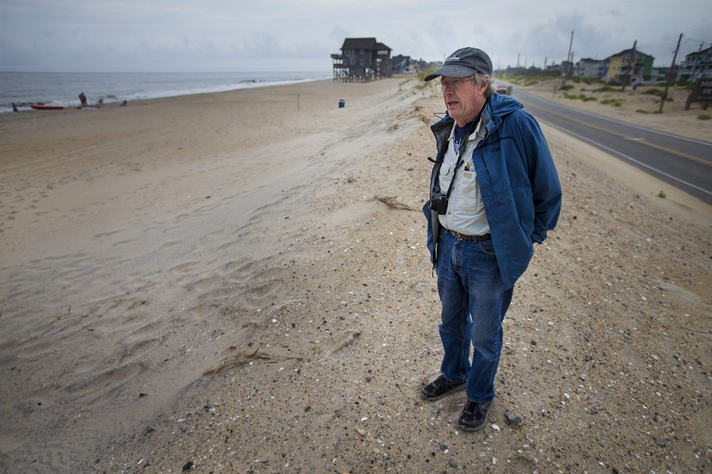 Stanley Riggs, of East Carolina University, stands on the edge of the Rodanthe Beach and Highway 12. (Jesse Costa/WBUR)