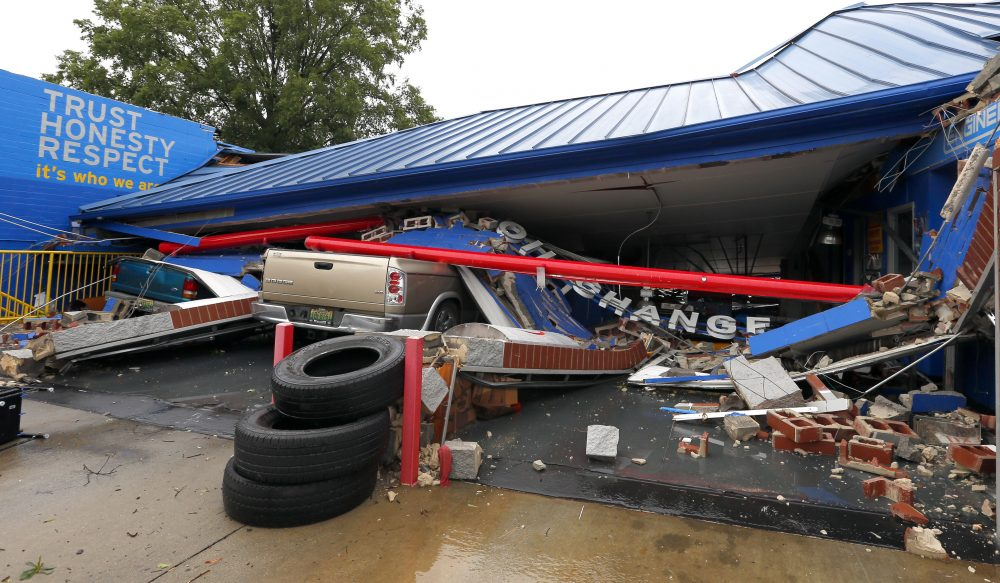 Several cars sit under the collapsed roof of an Express Oil Change after a possible tornado touched down destroying several businesses, June 22, 2017, in Fairfield, Ala. (Butch Dill/AP)