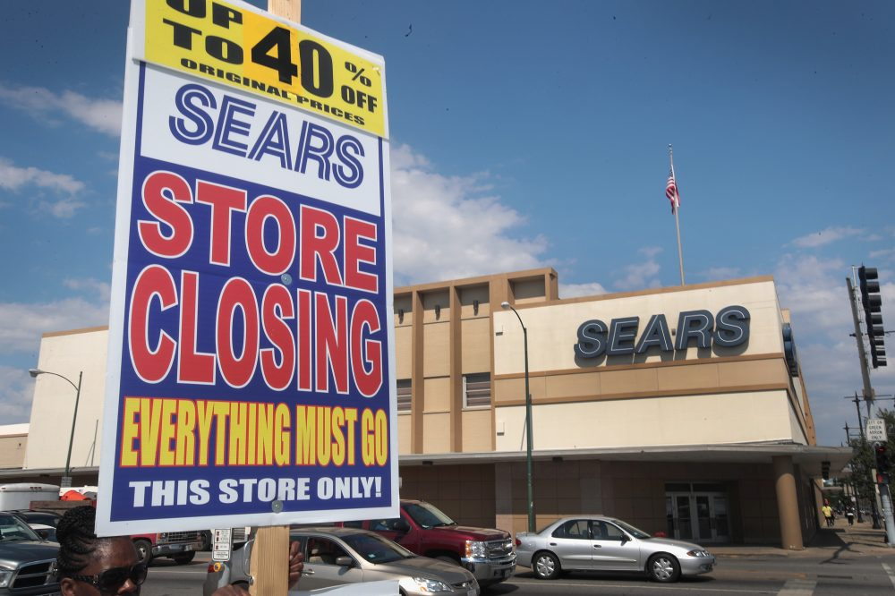 A worker holds a sign announcing a store-closing sale outside the 60-year-old Sears store in the Galewood neighborhood of Chicago on July 7, 2017. (Scott Olson/Getty Images)