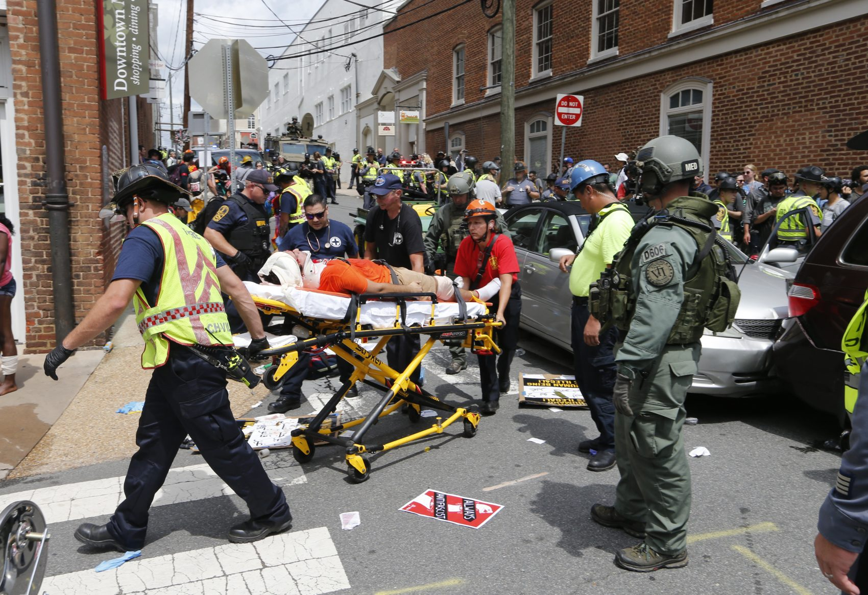 Rescue personnel help injured people after a car ran into a large group of protesters after an white nationalist rally in Charlottesville, Va., Saturday, Aug. 12, 2017. (Steve Helber/AP)