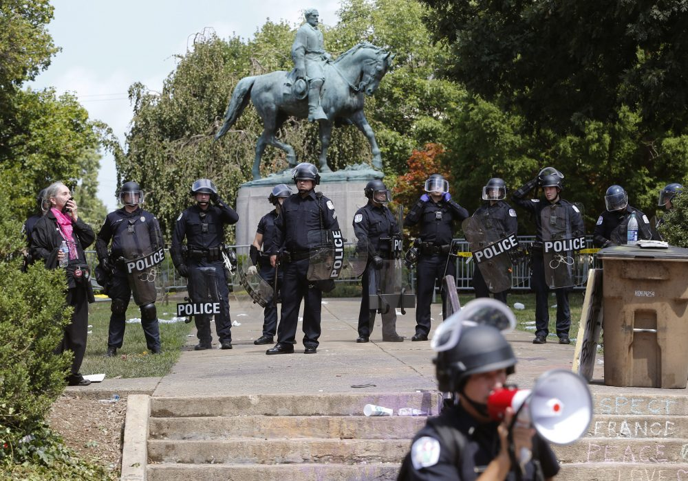 State Police in riot gear guard Lee Park after a white nationalist demonstration was declared illegal and the park was cleared in Charlottesville, Va., Saturday, Aug. 12, 2017.  Hundreds of people chanted, threw punches, hurled water bottles and unleashed chemical sprays on each other Saturday after violence erupted at the white nationalist rally. (Steve Helber/AP)