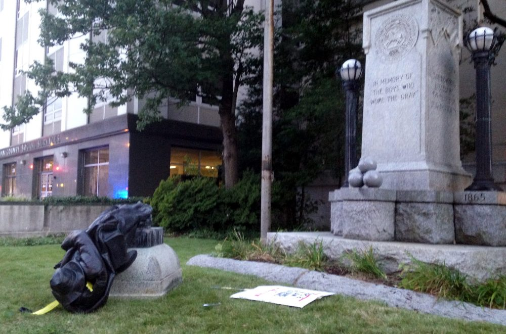 A toppled Confederate statue lies on the ground on Monday, Aug. 14, 2017, in Durham, N.C. Activists on Monday evening used a rope to pull down the monument outside a Durham courthouse. The Durham protest was in response to a white nationalist rally held in Charlottesville, Va, over the weekend. (Jonathan Drew/AP)