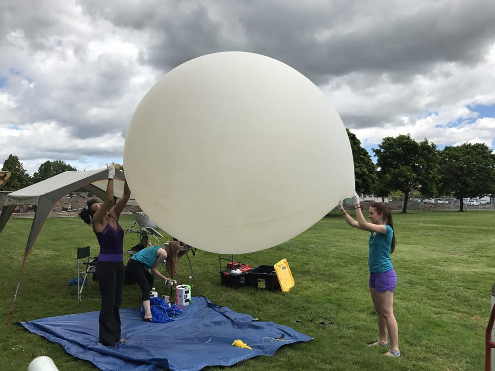 Earlier this summer, PSU students Rihana Mungin (from left), Harmony Ewing and Olea Stevens tested the type of weather balloon they'll use for the NASA-funded Eclipse Ballooning Project on Aug. 21. (Portland State University)