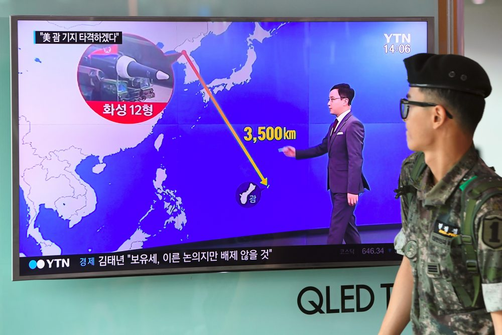 A South Korean soldier walks past a television screen showing a graphic of the distance between North Korea and Guam at a railway station in Seoul on Aug. 9, 2017. (Jung Yeon-Je/AFP/Getty Images)