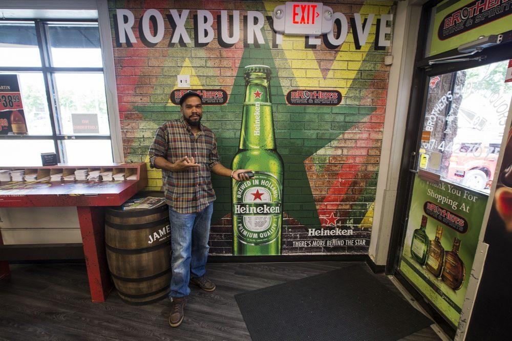 "Artist Thomas ""Kwest"" Burns in front of the Heineken advertisement inside Brother's Wine & Spirits in Roxbury, a few blocks away from the original on Warren Street. (Jesse Costa/WBUR)"