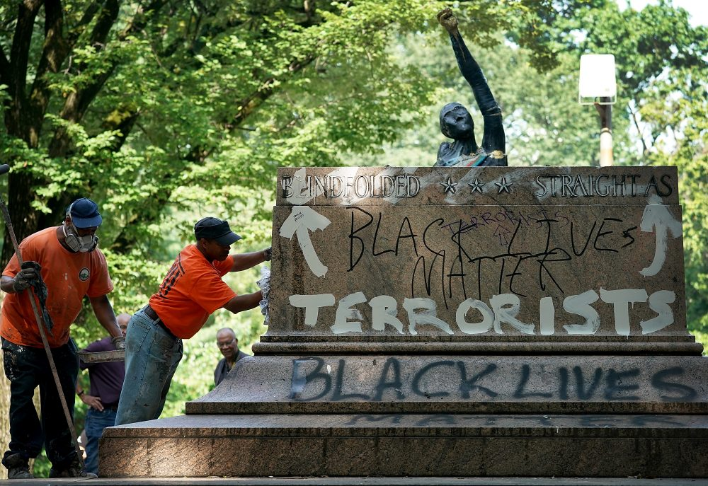"Baltimore city workers remove graffiti from the pedestal where a statue dedicated to Robert E. Lee and Thomas ""Stonewall"" Jackson stood Aug. 16, 2017 in Baltimore. The city removed four statues of Confederate heroes from city parks overnight, following the weekend's violence in Charlottesville, Va.  (Win McNamee/Getty Images)"