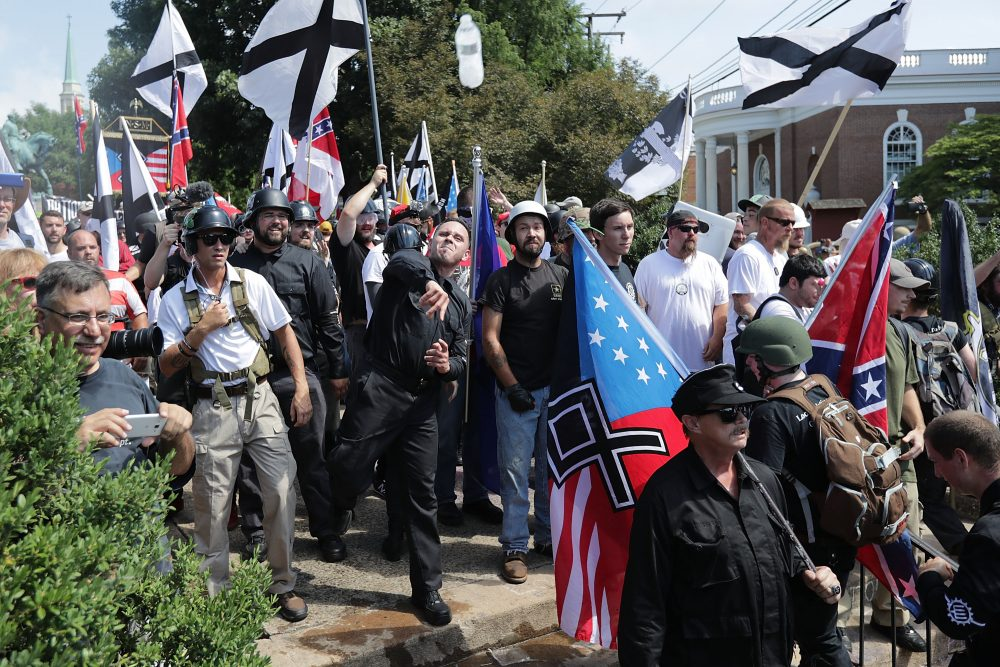 """Hundreds of white nationalists, neo-Nazis, KKK and members of the """"alt-right"""" hurl water bottles back and forth against counter demonstrators on the outskirts of Emancipation Park during the Unite the Right rally Aug. 12, 2017 in Charlottesville, Va. (Chip Somodevilla/Getty Images)"""