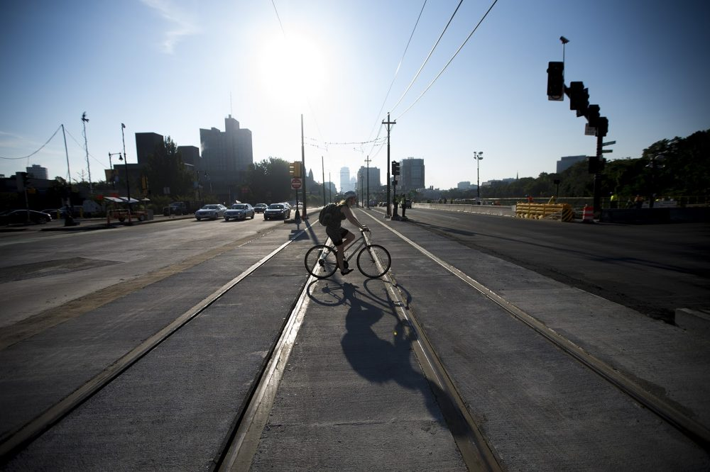 A cyclist crosses the Comm. Ave. Bridge Wednesday morning, the first day the road was reopened following three weeks of construction (Jesse Costa/WBUR)