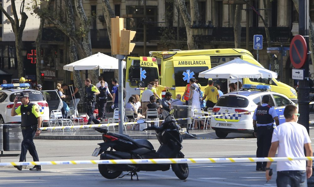 Injured people are treated in Barcelona, Spain, Thursday, Aug. 17, 2017 after a white van jumped the sidewalk in the historic Las Ramblas district, crashing into a summer crowd of residents and tourists and injuring several people, police said. (Oriol Duran/AP)
