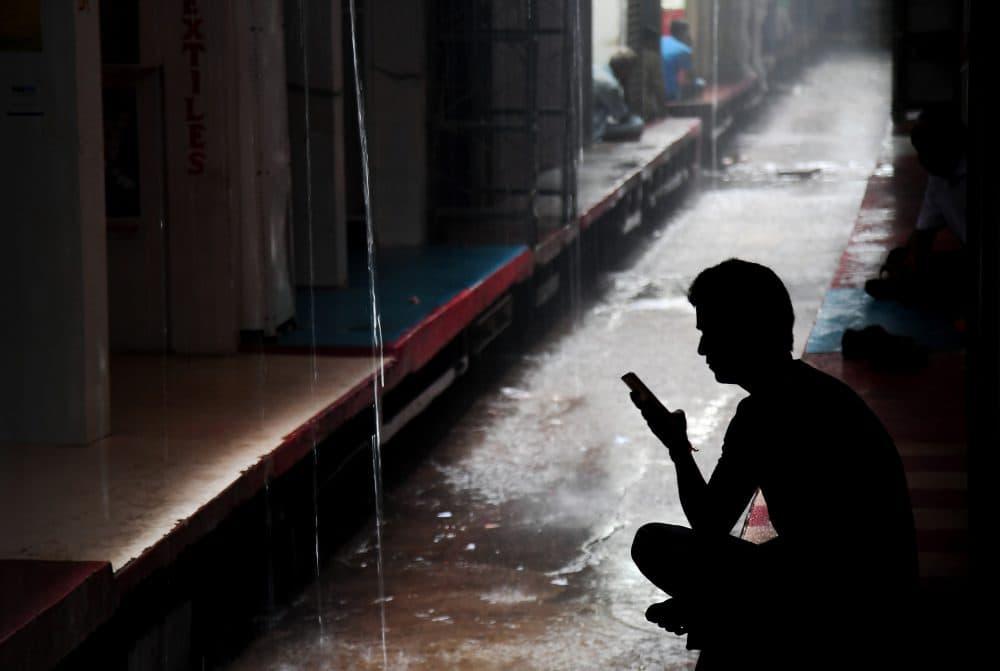 An Indian textile trader looks at his phone in Kolkata on June 30, 2017. (Dibyangshu Sarkar/AFP/Getty Images)