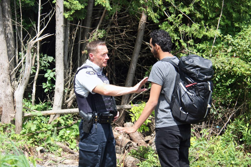 A Canadian police officer warns a young man from Yemen that if he illegally crosses into Canada in between checkpoints he will be arrested. If he proves to not be a threat to the public, the officers will help him fill out the asylum request paperwork. (Kathleen Masterson/VPR)