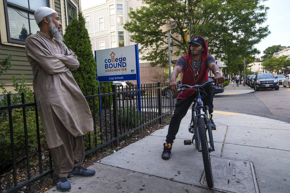 """Standing outside of the Bowdoin Street College Bound Dorchester facility, program coordinator Ismail Abdurrashid, left, speaks with a former College Bound student who asked to be identified only by his nickname, """"Streets."""" They discuss the prospects of him coming back to school and continuing his education. (Jesse Costa/WBUR)"""