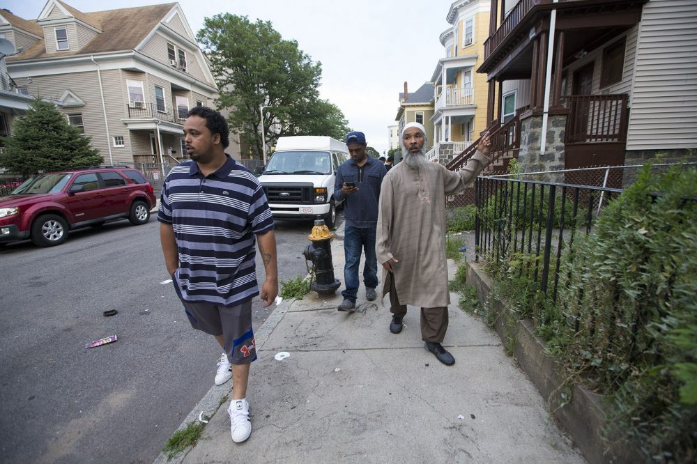 College Bound Dorchester facility program coordinator Ismail Abdurrashid, right, canvasses the Bowdoin-Geneva area with Malik Hobson, rear, and Francisco Depina, front, looking to engage the community and find at-risk youth to try to set them on the path to higher education. (Jesse Costa/WBUR)