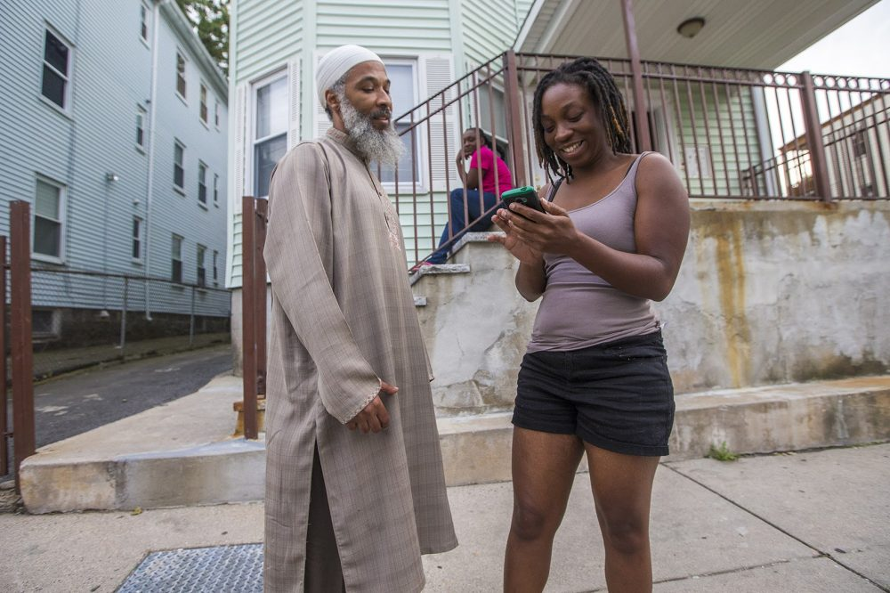 Abdurrashid catches up with Shanna Jackson, a former student at College Bound during a canvass through the Bowdoin-Geneva area. (Jesse Costa/WBUR)