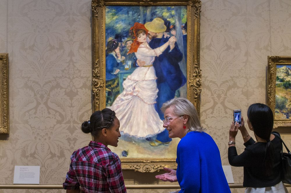 "Dorene McCourt describes impressionism to Hiwot Behabtu while they look at Renoir's ""Dance at Bougival."" (Jesse Costa/WBUR)"