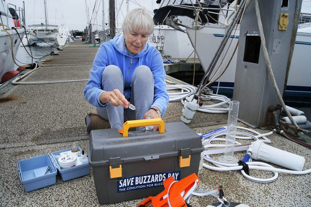 Chris Parks, a volunteer for the Buzzards Bay Coalition, tests water conditions at Fairhaven Shipyard near New Bedford. (Lynn Jolicoeur/WBUR)