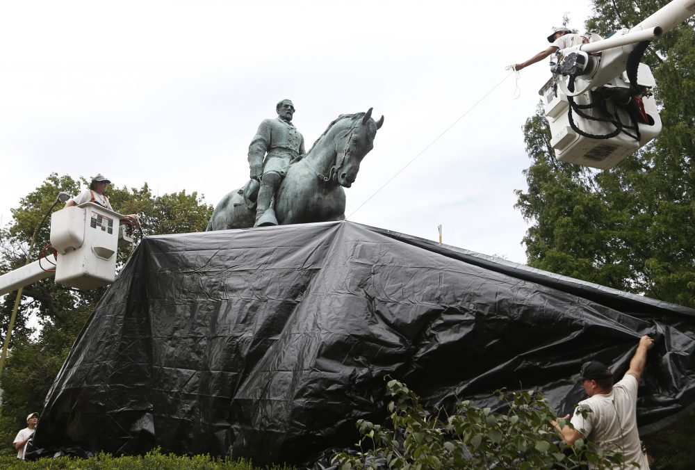 City workers drape a tarp over the statue of Confederate General Robert E. Lee in Emancipation park in Charlottesville, Va., Wednesday, Aug. 23, 2017. (Steve Helber/AP)