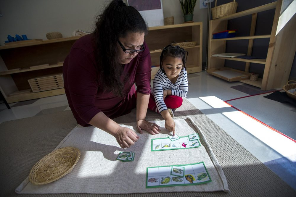 Tia Pocknett assists a student with a matching game involving images of birds and frogs. (Jesse Costa/WBUR)