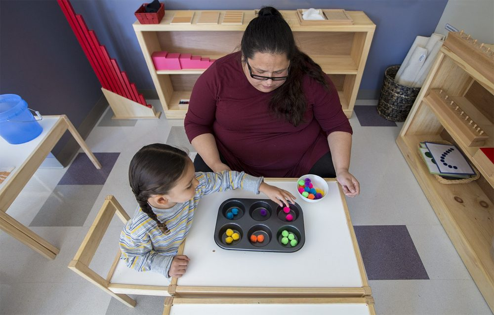 Linguist and teacher Tia Pocknett plays a color matching game with a young student. She calls out the Wampanoag names of colors as the student as she is matching the colored balls. (Jesse Costa/WBUR)